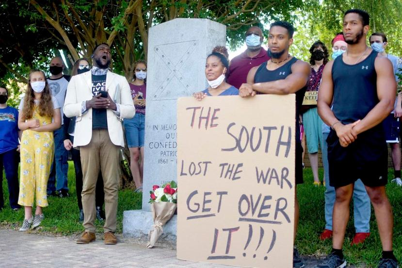 Crowd of young people stands by Walker County's Confederate monument with signs saying, 'The South lost the war, get over it!'