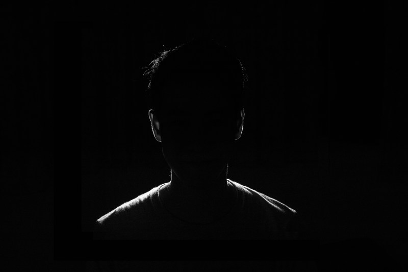 Anonymous person in dark room.