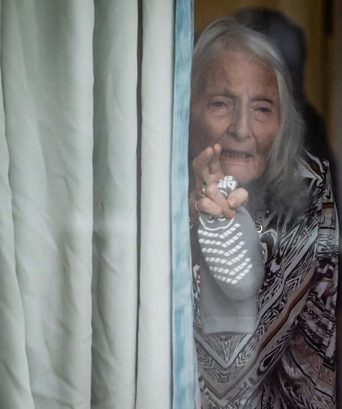 An elderly woman waves from behind a curtain