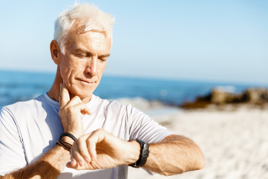 Middle-aged man checking his pulse after exercising.