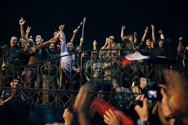 Zivilisten und Soldaten in Uniform, die Waffen halten, jubeln nachts auf einem Balkon