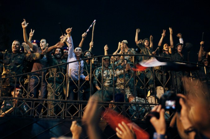 Civilians and soldiers in fatigues holding weapons cheer on a balcony, at night