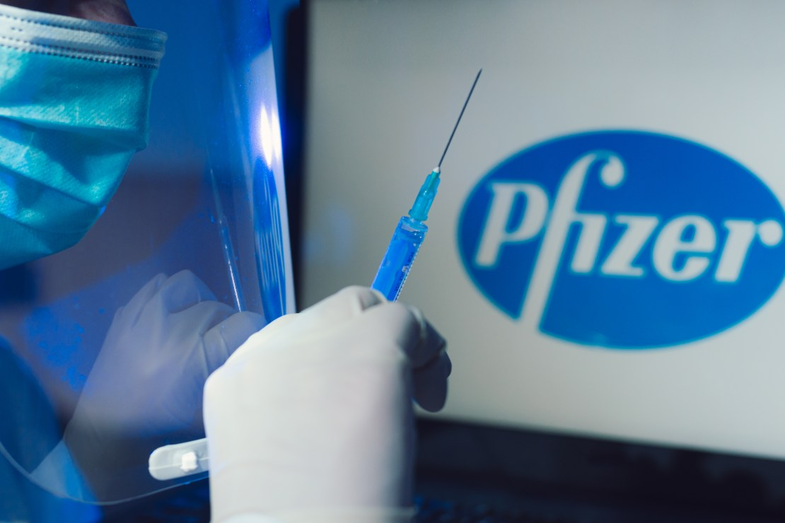 Medical gloved hand holds syringe in front of Pfizer logo