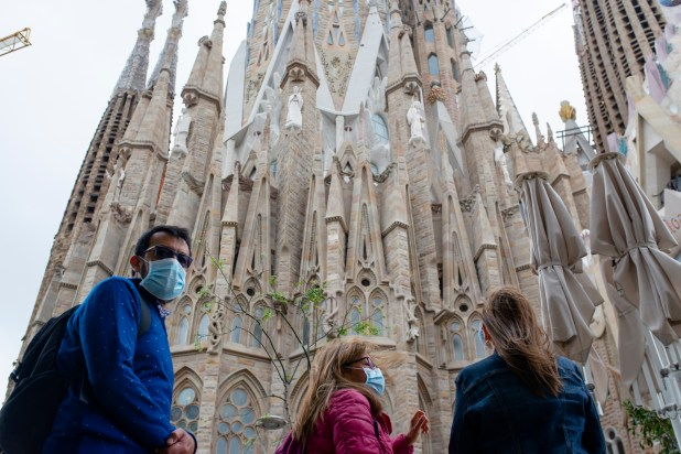 Three people wearing masks standing in front of La Sagrada Familia cathedral in Barcelona, Spain.