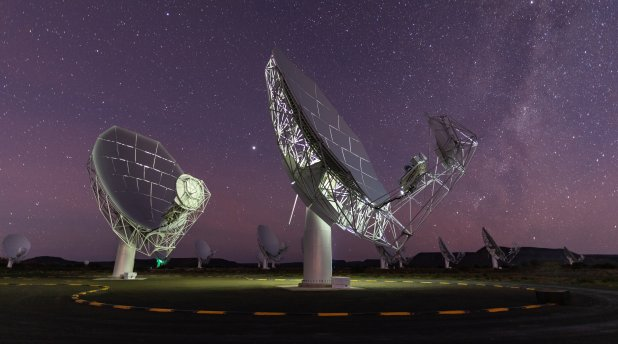 Two massive satellite dishes are pointed up towards the night sky