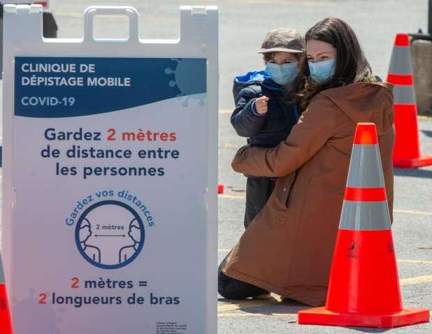 امرأة ترتدي قناع وجه تحتضن طفلها، أيضاً في قناع وجه، في موقف للسيارات خلف لافتة لاختبار COVID-19.
