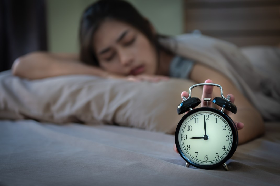 Teen girl waking up in bed and switching off alarm clock.