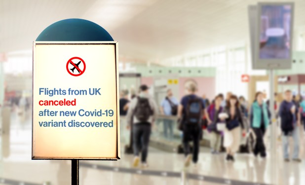 A sign at an airport saying flights from UK cancelled after new COVID-19 variant discovered,