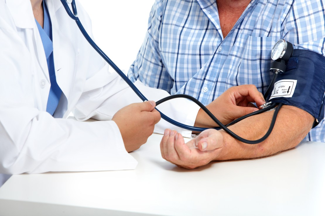 A patients blood pressure being taken by a doctor.