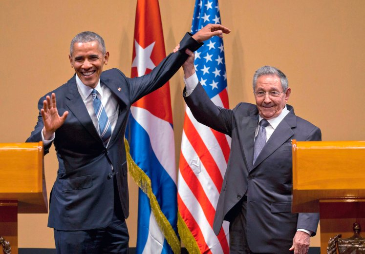 Raul Castro lifts Barack Obama's arm.