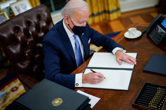Biden signing an executive order at the Resolute Desk