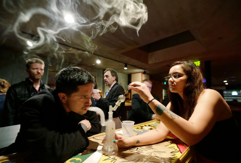 A man inhales marijuana smoke from a glass bong in a room with other people around.