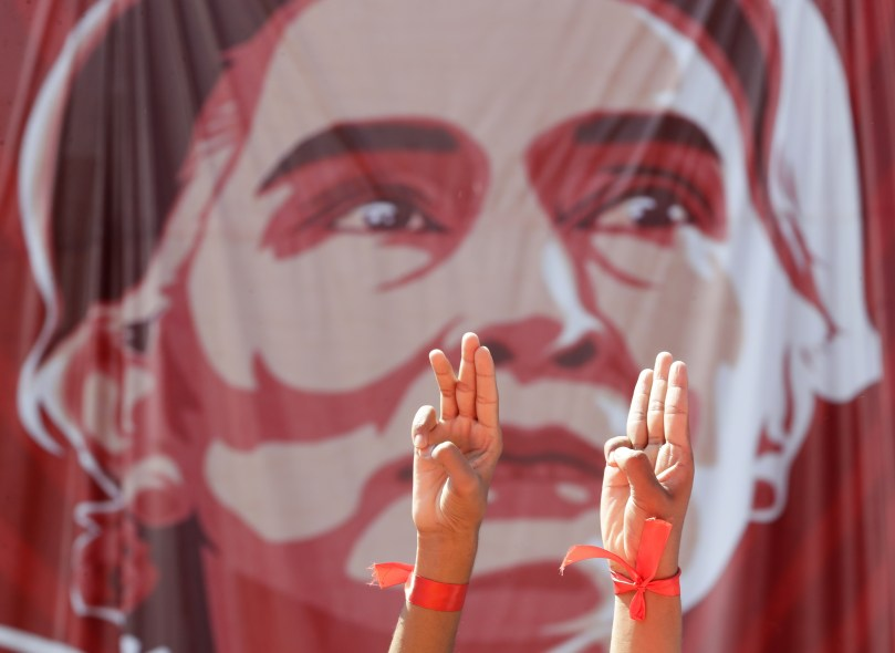 Poster of Aung San Suu Kyi with three-fingered salute of protester defiance in the foreground.