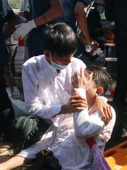 Person wearing white shirt and face mask hold another lying down with wet hair