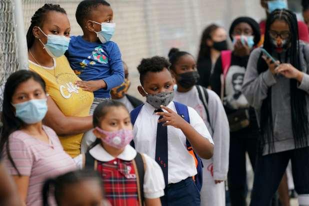 الأطفال والآباء ينتظرون خارج مدرسة في مدينة نيويورك يرتدون أقنعة.