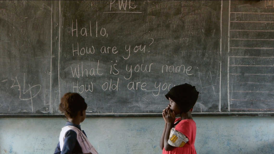 Two children in front of a blackboard showing English phrases.