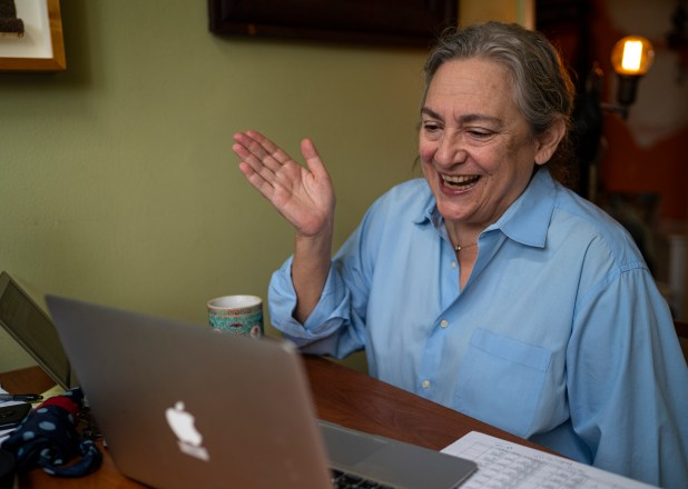 A woman smiles while looking at her laptop.