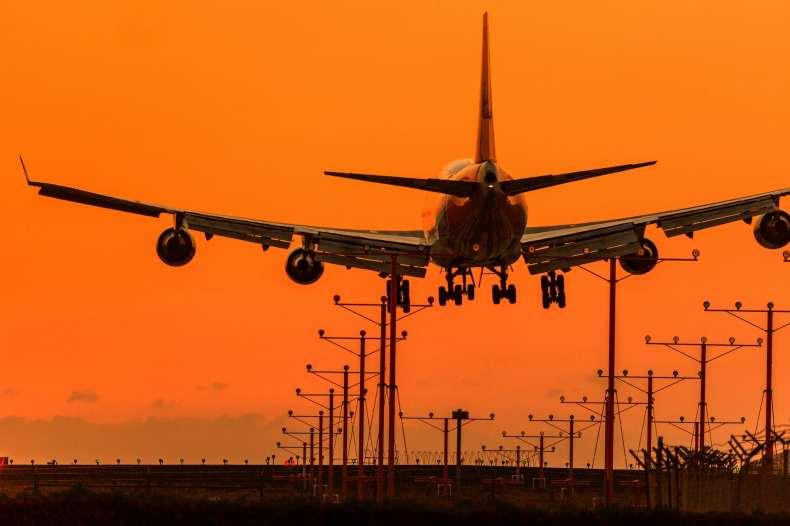Plane lands at sunset