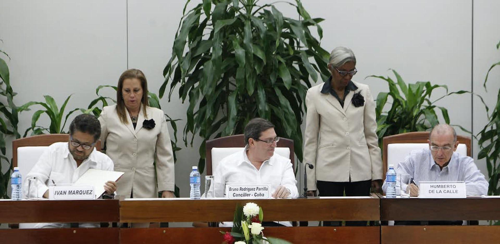 Humberto de la Calle, negociador del Gobierno colombiano, y Luciano Marín, rebelde de las FARC, firman un acuerdo de paz en la Habana (Cuba)