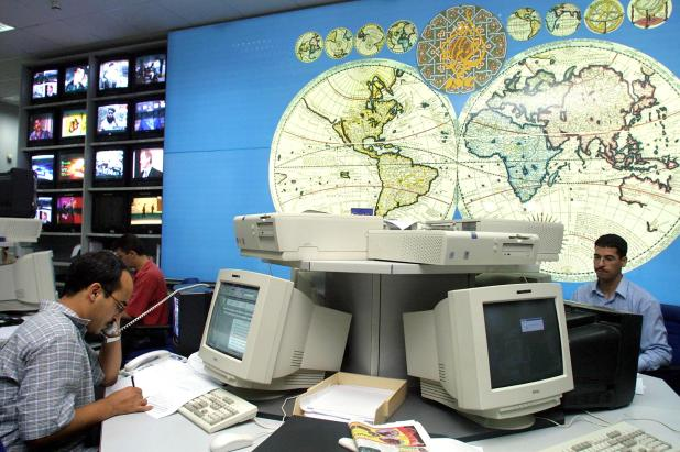 Two journalists sit in a newsroom with old desktop computers and a world map on the wall