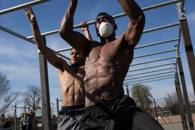 Two men using exercise bars outdoors.