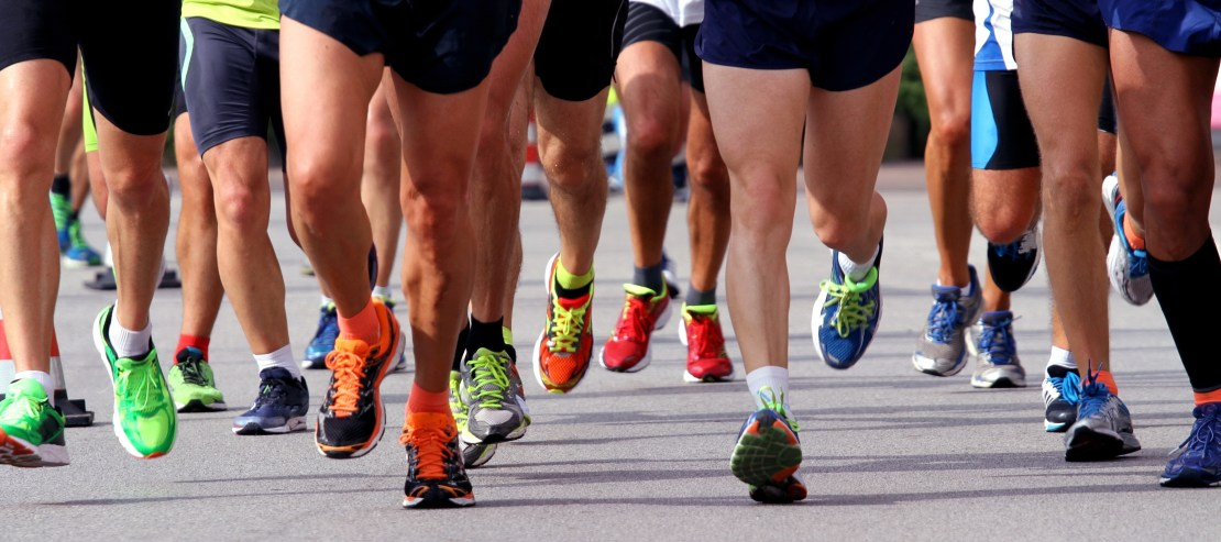 Many runners' legs and shoes running on tarmac