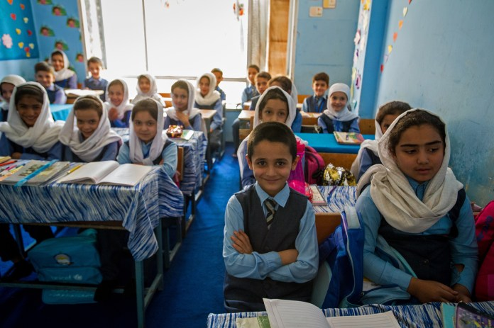 Sunny, blue-painted classroom full of smiling Afghan boys and girls