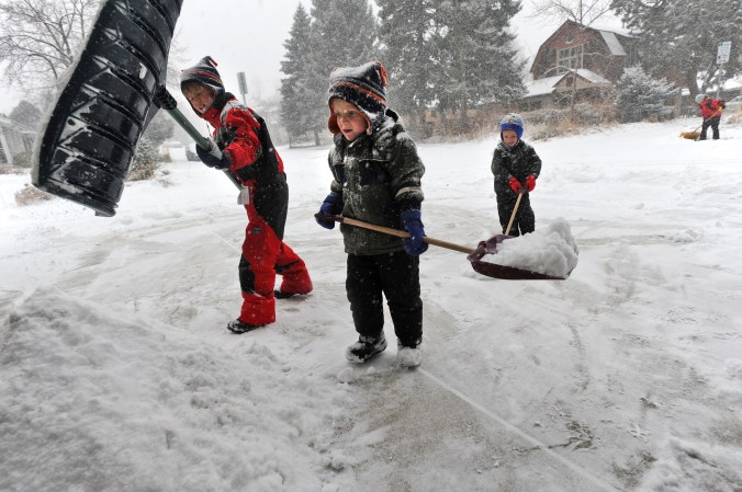 Young children shovel snow