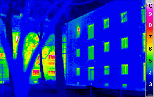 A thermal image of a house showing hotspots of heat leaking out of windows.