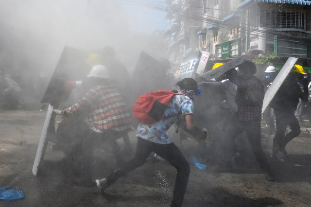 People with shields and hard hats duck and run for cover on a smoky street