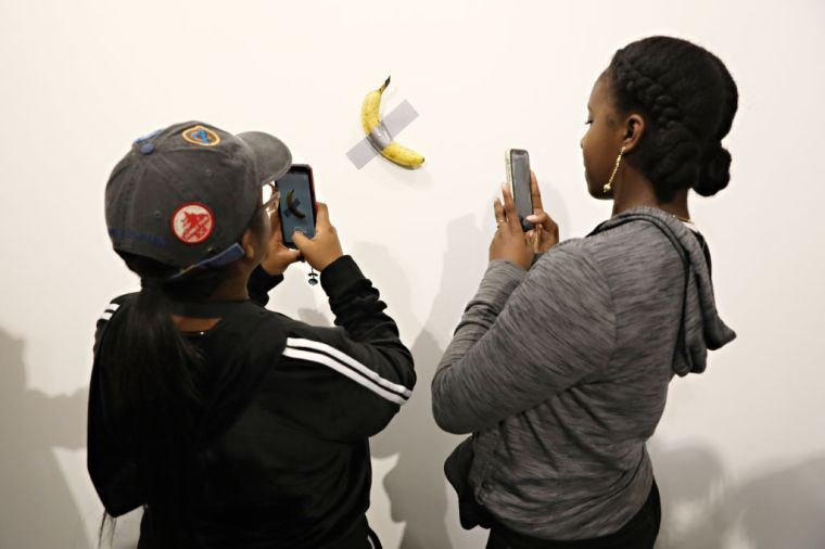 Two people take photographs with their smartphones of a banana taped to a wall.