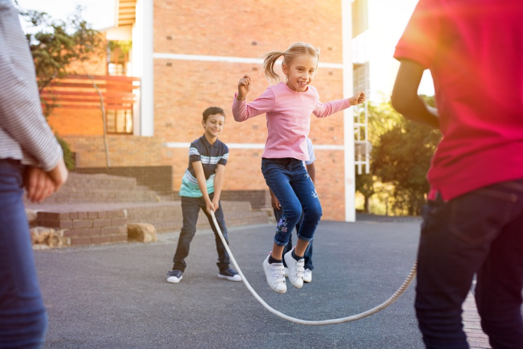Kids playing jump rope with teacher watching.