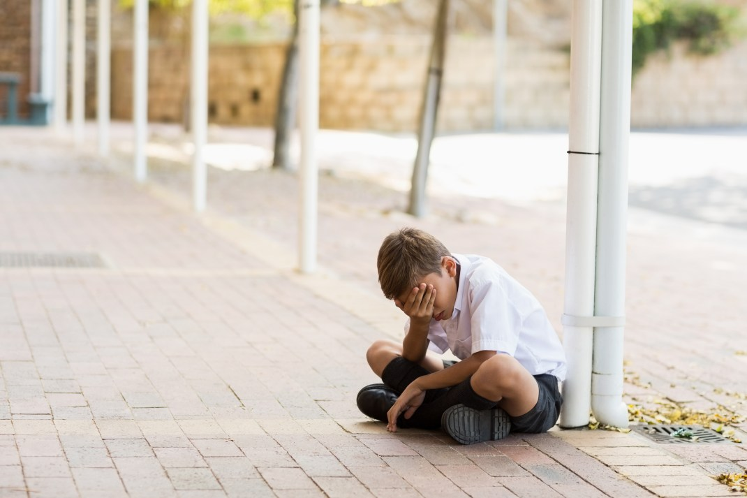 Sad schoolboy sitting on the ground with head in hands.