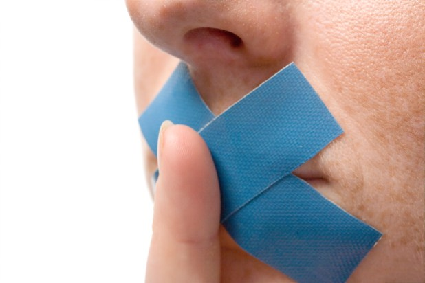 Person with blue tape over their mouths holds finger to lips