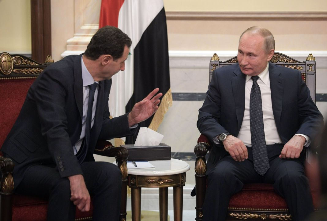 Bashar as-Assad and Vladimir Putin seated and talking