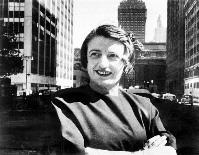 Ayn Rand sits with her arms folded outside Grande Central Terminal in New York City