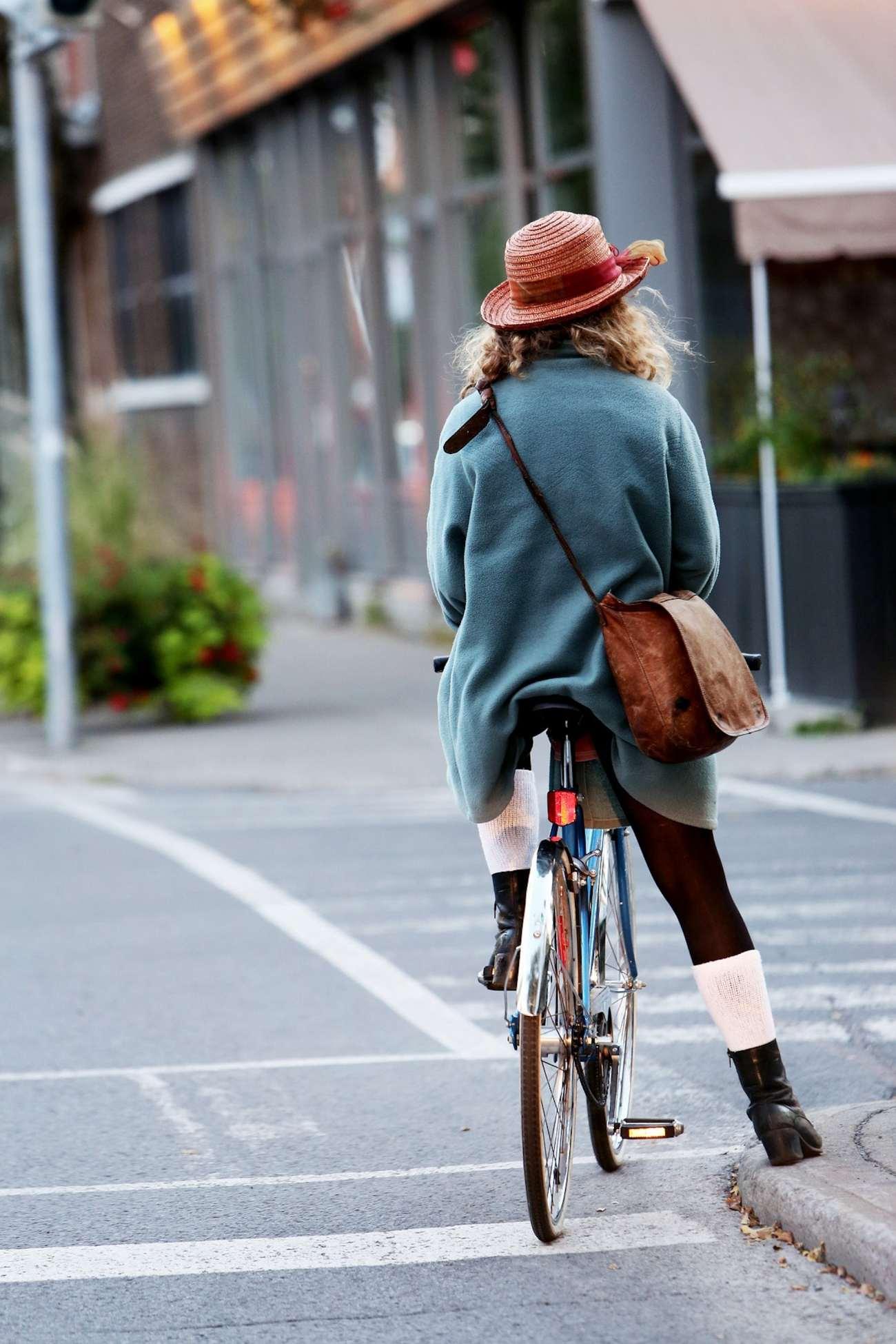 Donna con un cappello in bicicletta, ripresa da dietro