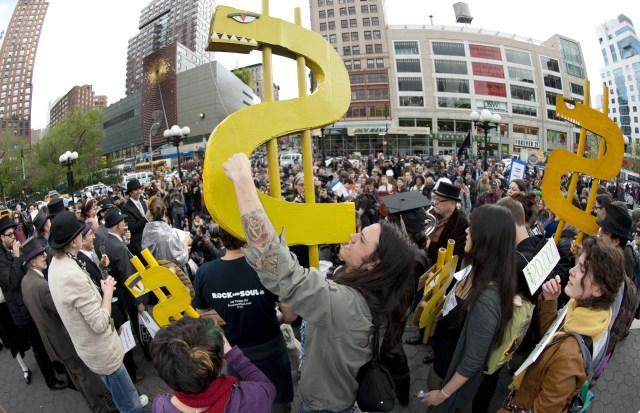 A man holds up a dollar sign during a rally against the high cost of college tuition in New York in 2012.