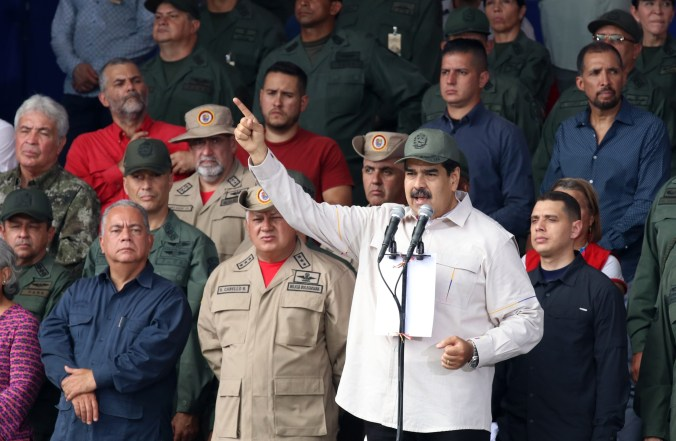 Maduro in a military hat surrounded by soldiers speaks at a microphone with his hand raised
