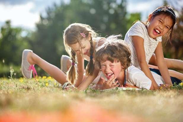 ثلاثة أطفال يضحكون في حزمة على بعض العشب