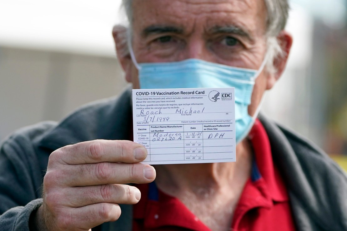 masked older man holds up his vaccination card