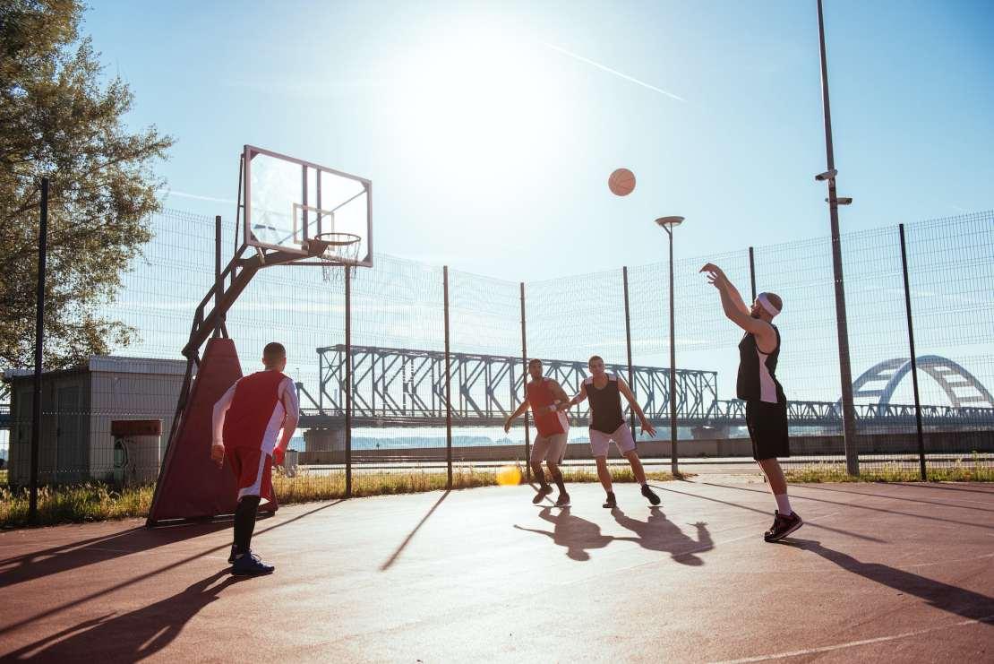 Five men play basketball outdoors.