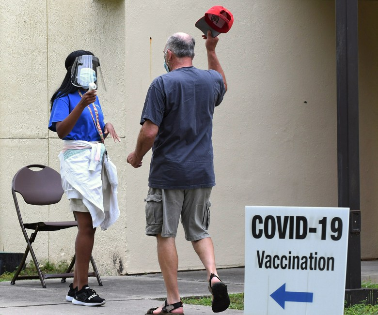 man removes hat for temperature check at COVID-19 vaccination site