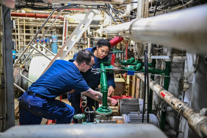 Two Coast Guard crew members, a man and a woman, work amid pipes on the ship.