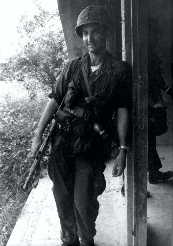 Daniel Ellsberg leans against a pole wearing army fatigues and holding a gun.