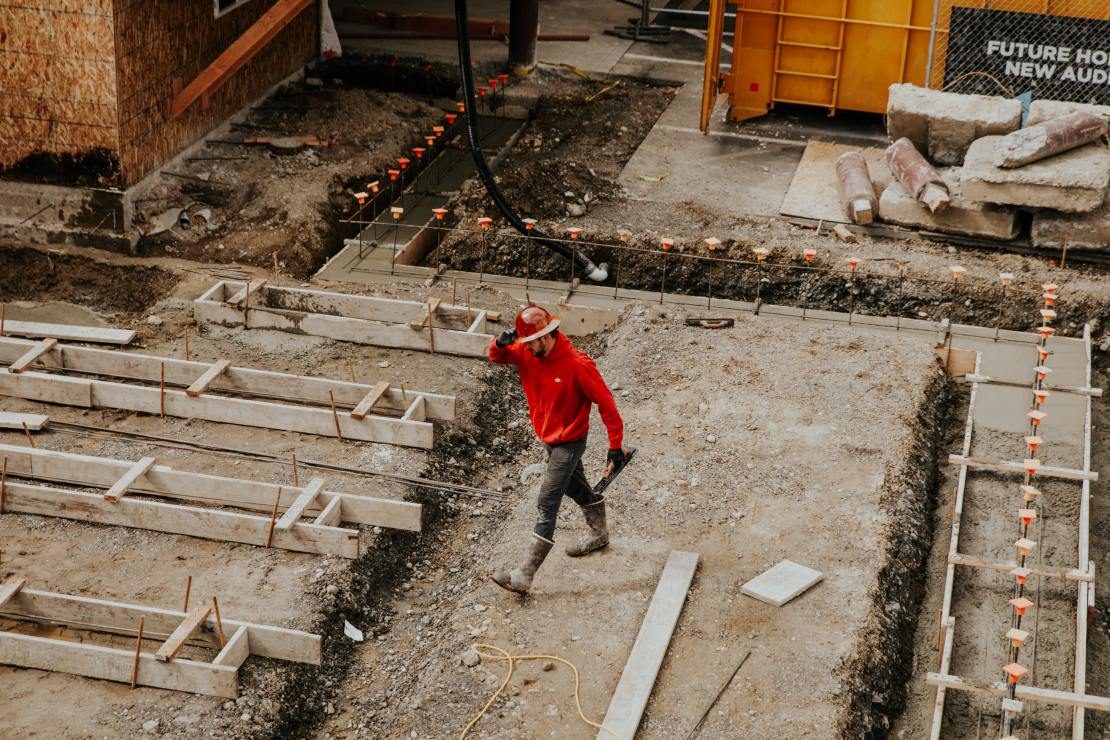A man in a red top and hard hat walks across a construction site