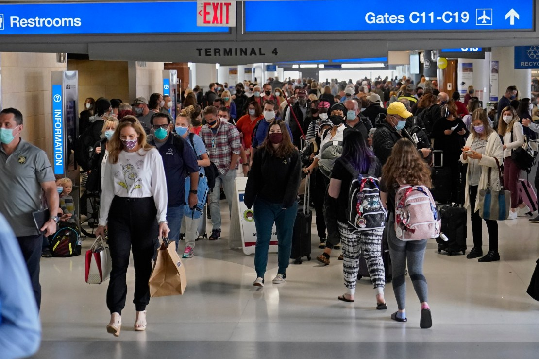 Masked passengers moving through airline terminal