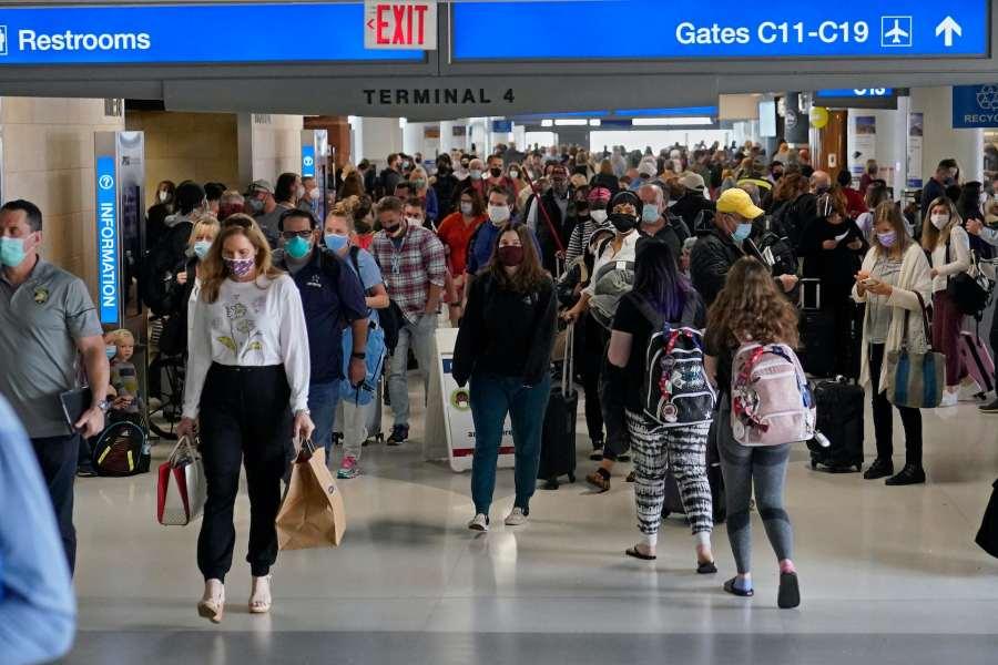 Pasajeros enmascarados moviéndose a través de la terminal aérea