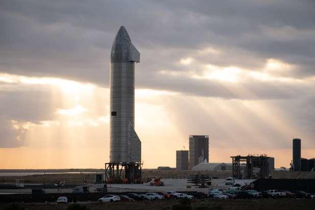 صاروخ فضي كبير يقف منتصباً على منصة الإطلاق.