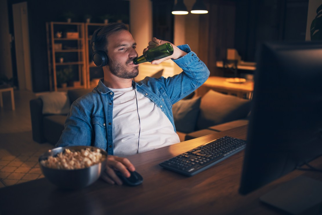 Young man drinks a bottle of beer with a snack at night in front of his computer.